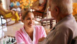 Man in geriatric hospice speaking with his nurse.