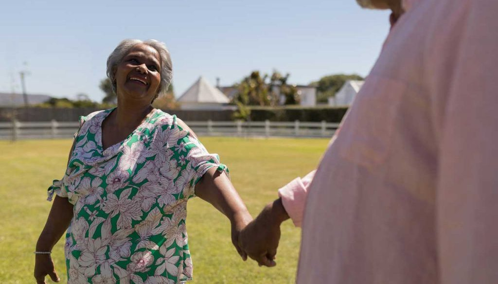 elderly woman and man holding hands and dancing with each other