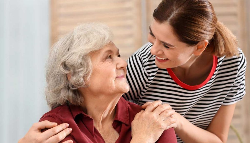 elderly woman sitting at home and smiling while receiving comfort from a hospice volunteer