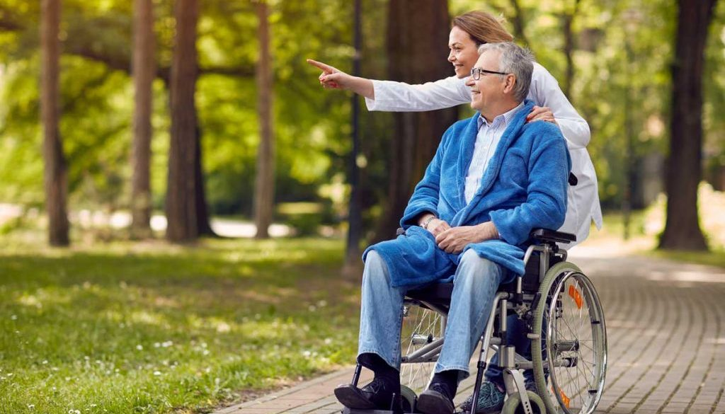 elderly man on hospice smiling and being are being pushed in wheelchair around the park by his caregiver