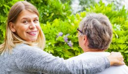 smiling hospice caregiver with elderly woman on bench overlooking beautiful greenery
