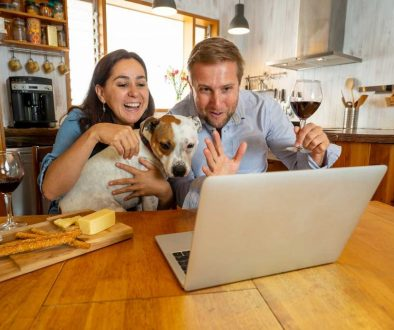 young couple with dog smiling and video chatting with grandparent in hospice care