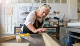elderly woman starting a new hobby by woodworking in a workshop