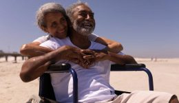 smiling man in hospice care using a wheelchair with his wife's arms wrapped around him enjoying the sun at the beach