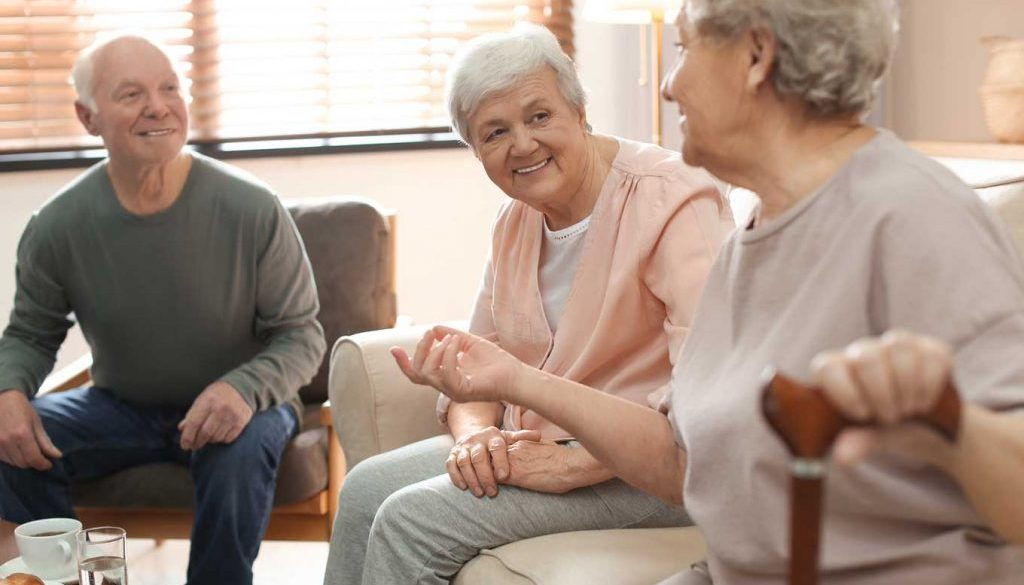 group of elderly people sitting and smiling together in hospice care